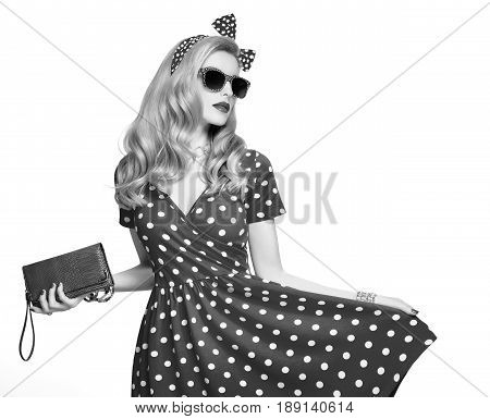 Fashion Model Girl in Polka Dots Summer Dress. Stylish Curly hairstyle, Trendy Clutch, fashion Headband, Sunglasses. Beauty Blond Pinup Woman in fashion pose. Glamour Playful Sexy Lady.Black and White