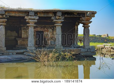 View of ancient ruins on Hemakuta hill in Hampi, Karnataka, India. Landscape with amazing stones tropical nature and temple. UNESCO World Heritage Site