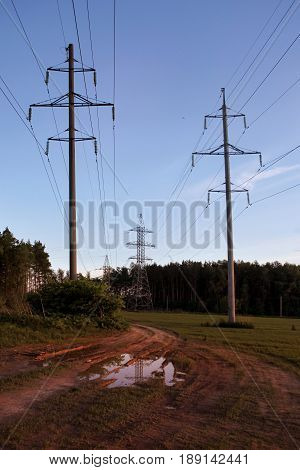 High-voltage line in the field/ Autumn day, mud and puddles