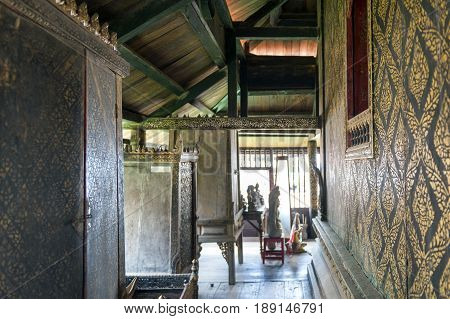 Yasothon Thailand - May 2017: Interior decoration with gilded black lacquer or Lai Rod Nam on walls and scripture cabinets inside Ho Trai or the Buddhist scriptures (Tripitaka) library located at Wat Mahathat Temple