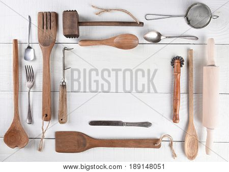 Top view of a group of cooking utensils on a rustic wood kitchen table arranged around a blank space for your copy.