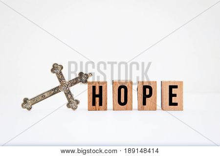 Hope in wooden block letters with silver cross on white background