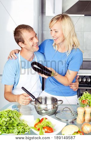 beautiful happy young couple cooking   eggplant in the kitchen at home