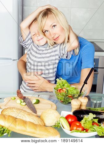beautiful happy young mother and son cooking   in the kitchen at home