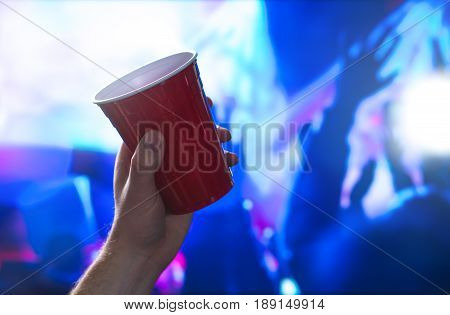 Young man holding red party cup in nightclub dance floor. Alcohol container in hand in disco. College student having fun and dancing. Celebrating people in the back. Event marketing and promotion.