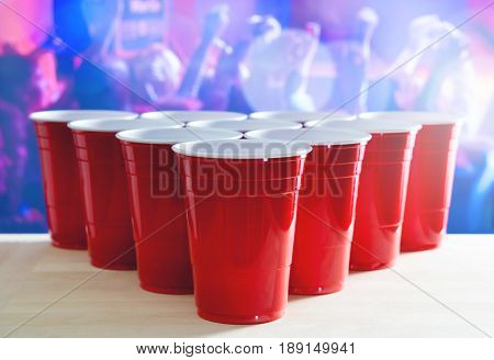 Beer pong tournament layout. Many red party cups in a nightclub full of people dancing on the dance floor in the background. Perfect for marketing and promotion for event. Plastic mugs on wooden table