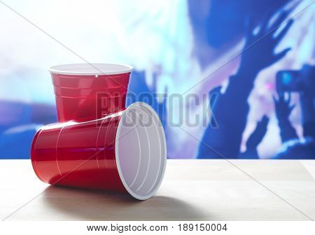 2 plastic red party cups on a table. One on its side. Nightclub or disco full of people dancing on the dance floor in the background. Perfect for marketing and promotion for events or college fest.