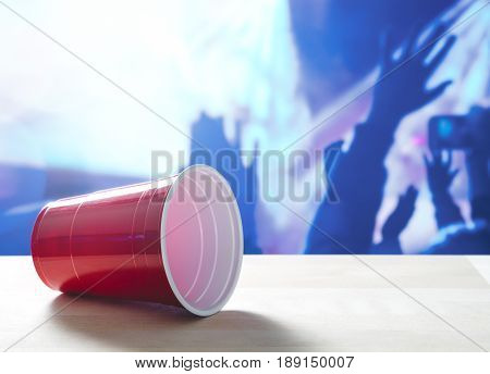 Fallen plastic red party cup on its side on a table. Nightclub or disco full of people dancing on the dance floor in the background. Perfect for marketing and promotion for events or college fest.