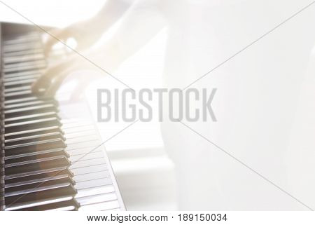 Blurry abstract music background. Wallpaper for piano lessons, training, coaching and talent show with free empty blank copy space for text. Man playing instrument. Yellow lens flare from sun light.