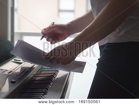 Musician brainstorming and innovating new song ideas at piano by the window. Composer writing notes to paper or planning arrangement. Man come up with pop lyrics. Inspiration and creativity concept.