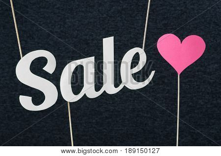 Sale text cut from cardboard paper on wooden stick and dark background. Marketing material for valentine's, women's or mother's day special offer or campaign prices. Nice and fun banner for website.
