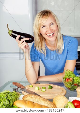 beautiful happy young woman cooking eggplant in the kitchen at home