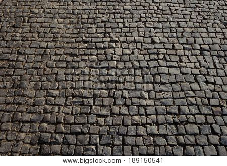 Texture of square black cobblestone pavement surface