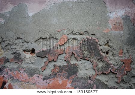 Weathered concrete wall with damaged stucco and old paint