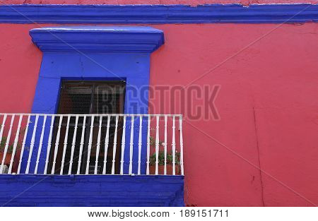 Small balcony in blue and pink, in the historic city of Oaxaca, Mexico