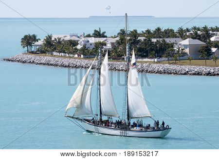 The ship passes by Sunset Key artificial island in Key West town (Florida).