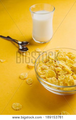 Corn Flakes And Milk On A Yellow Background. Breakfast Concept