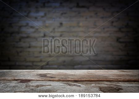 Selected focus empty old wooden table and wall texture or old black brick wall blur background image. for your photomontage or product display