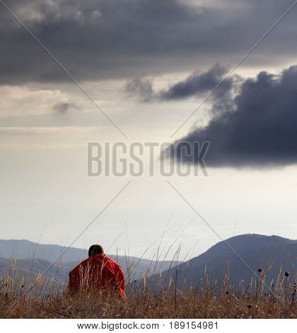 Man resting at mountains in sun evening