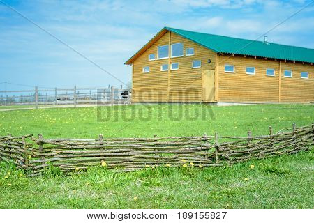 A Braided Wooden Fence Made Of Thin Branches In The Countryside Against Green Lawn At The Neat Ostri