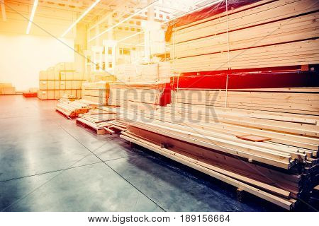 sawn wood. Shelf with structural materials on the shelves in the construction warehouse. Concept logistics companies and large  warehouse industrial. high contrast and monochrome color tone.