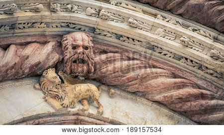 Gothic relief and lion statue in Siena Italy