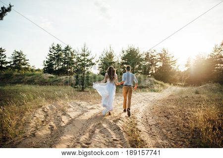 Just married loving hipster couple in wedding dress and suit on green field in a forest at sunset. happy bride and groom walking running and dancing in the summer meadow. Romantic Married young family