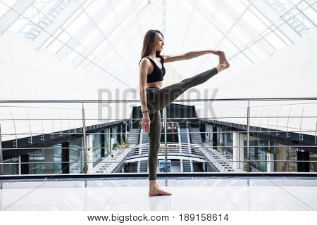Extended Hand-to-big-toe Pose. Beautiful Yoga Woman Practice In A Big Business Hall Background. Yoga