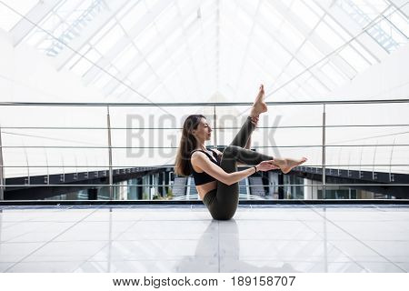 Beautiful Yoga Woman Practice In A Big Business Hall Background. Yoga Concept.