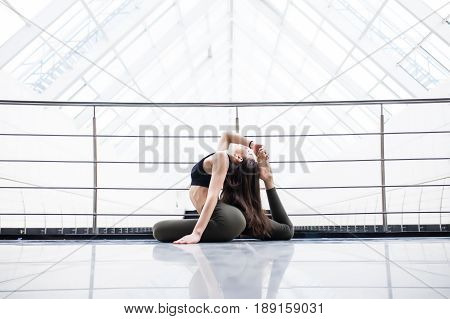 One-legged King Pigeon Pose. Beautiful Yoga Woman Practice In A Big Window Hall Background. Yoga Con