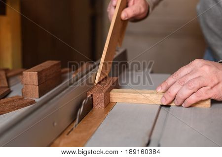 Carpenter sawing wooden plank by circular saw helping with stick for safety working