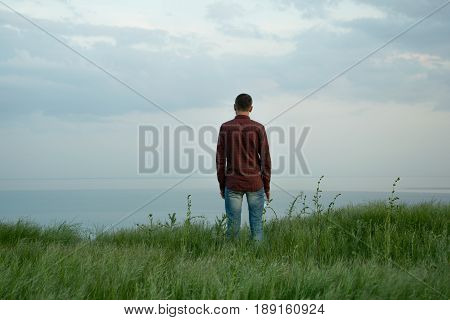 Young man stands on the edge of a precipice. Back view young male. Landscape grass steppe. Travel Concept.sea