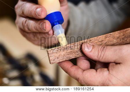 Carpenter applying glue on wooden detail closeup