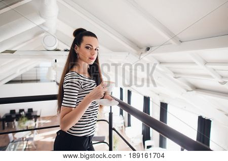Close up portrait of a girl with brown hair holding take away coffee cup and smartphone while looking at the camera