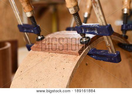 Part of handmade wooden drum held in clamp closeup