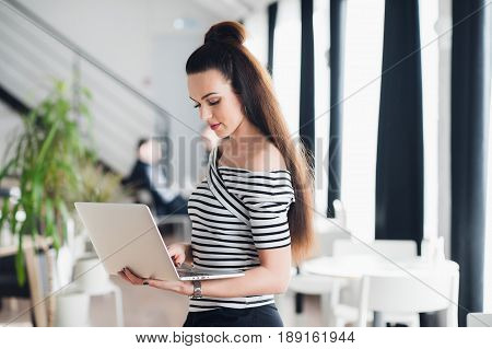 Charming female is using mobile phone and laptop computer while sitting in modern coffee shop interior, young beautiful hipster girl holding cell telephone during work on portable net-book