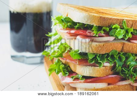 Homemade Sandwich With Ham And A Glass Of Dark Beer On An Old Shabby Background