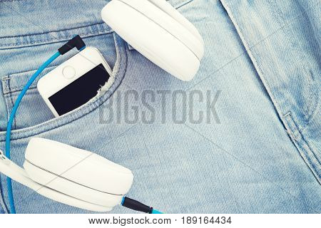 White headphones and smartphone in the pocket of jeans. Listen to music everywhere