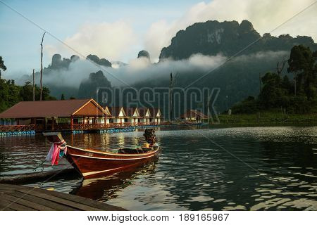 Scenic and unique landscape with floating houses and long tail boats at Chieou Laan lake Thailand
