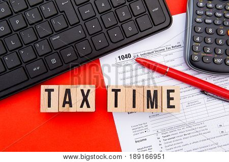 Tax Time - USA - wooden letters with 1040 Tax Form, keyboard and calculator