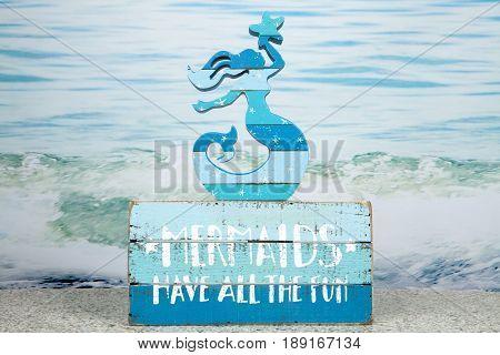 A mermaid themed still life against an ocean background