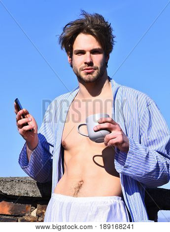 Bearded man short beard. Caucasian macho with moustache and ruffled hair in blue striped pajamas holding cup with cell phone in roof and show strong torso with six packs on blue sunny sky background