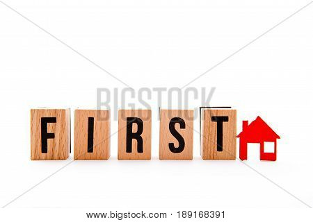 First Home - wooden block letters and red home icon on white background