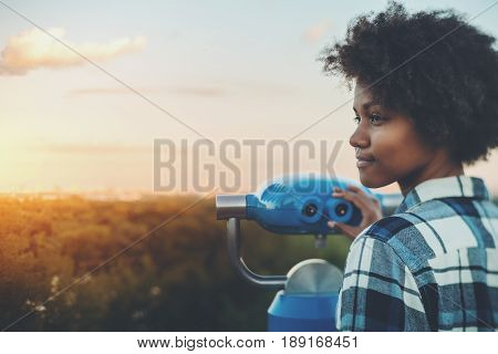 Tilt-shift portrait of meditative young black female with afro curly hair standing in high observation point and holding blue binocular with copy space zone for text logo or your advertising sunset