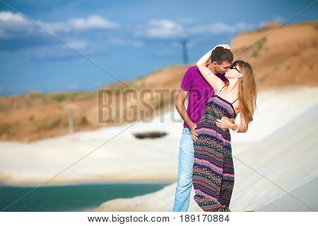 tender lovers on romantic travel honeymoon vacation summer holidays romance. Young happy couple on the beach with white sand, caucasian woman and man embracing and kissing outdoors