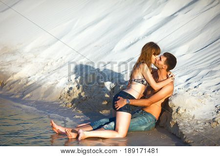 in love couple on romantic travel honeymoon vacation summer holidays romance. in love girl and man kissing and embracing on ocean shore