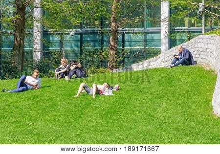 London UK - May 10 2017 - People sitting and lying on grass in Jubilee Park Canary Wharf on a sunny day