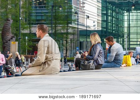 People Sitting On A Low Wall Outside Canary Wharf Tube Station
