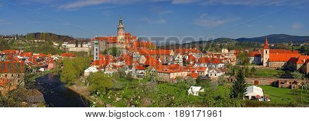 Panoramic view on old antique buildings orange roofing of castle Cesky Krumlov and city buildings. Castle towers on green hills and rocks. Traditional european architecture. Sightseeing places tours