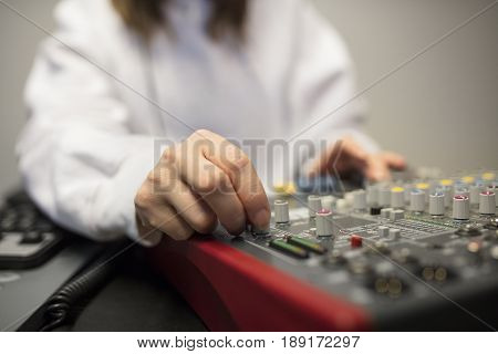 Midsection of female radio host's hand using music mixer in radio studio